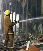 Firefighters damp down at the �100m centre