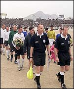 Match officials lead the teams out