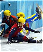 Apolo Anton Ohno (c), Mathieu Turcott (l) and Hyun-Soo Ahn crash out