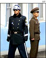 A South Korean soldier (left) and a North Korean (right) stand guard at the border line