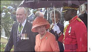 The Queen shielded from the rain in National Heroes Park in Kingston
