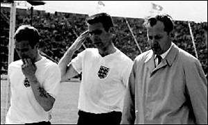 Sir Walter (right) leaves the field with England players Ray Wilkins and Peter Swan