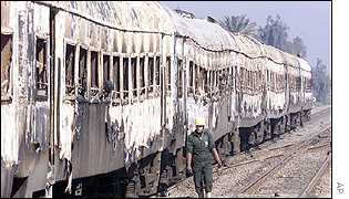 Rescue worker walks beside charred carriages