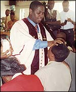 Reverend Stephen laying his hands on a follower's head