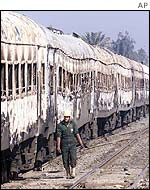 Rescuer walks past the burned out train