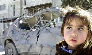Young Palestinian girl walks past car hit by Israeli air strike