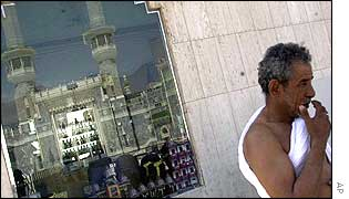 A Muslim pilgrim prays near the grand mosque, reflected in a window behind him