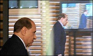 Silvio Berlusconi in front of TV screens