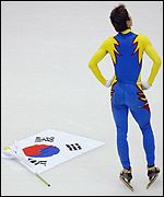Kim Dong-Sung stands in disbelief after throwing the South Korean flag to the ground following his disqualification