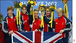 Great Britain's curlers stand on the podium after victory