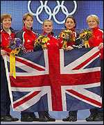 The British team hold up the Union Jack with their gold medals