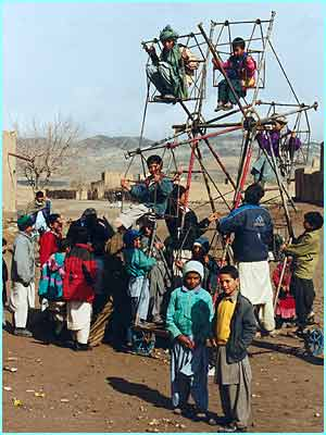 Children play on a ferris wheel in the village of Is-ak Sulema