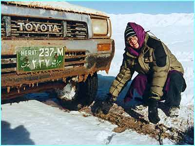 Audrey fixes the snow chains back on the truck
