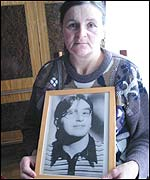 Marie Julien holds a picture of her sister, Madelein Dejust, whose body was found on the banks of the River Sereign