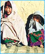 Golshah, 12, with her younger sister in their village called Kharistan