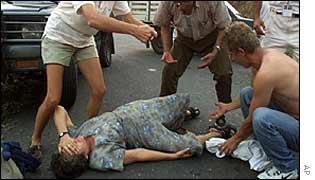 woman shot by rebels lies at a guerrilla road block