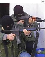Two Palestinian gunmen point M16s near the Balata refugee camp in the West Bank town of Nablus
