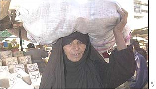 A woman carries a sack of food in Baghdad