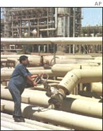 An Iraqi oil worker at an oil installation at Beiji in northern Iraq. Oil exports have dropped by 24%
