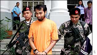 Fathur Rohman Al-Ghozi is escorted to the Philippines Department of Justice