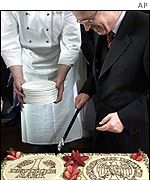 German Finance Minister Hans Eichel  cut a cake with the D-Mark currency emblem