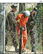 A prisoner is moved by guards at the Guantanamo Bay prison camp