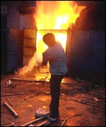 Shop owner Patel fights the flames after a wood market was set ablaze in Ahmedabad