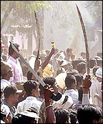 A Hindu mob waves swords at a Muslim mob