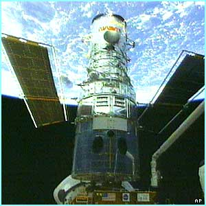 The Hubble Space Telescope sits in the cargo bay of the space shuttle Discovery orbiting the Earth