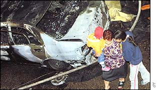 A family passes a burned car