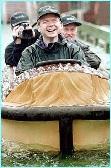 Ex-Conservative Party leader William Hague wearing his baseball cap (front ways - tut) and riding a log flume - not a chance!