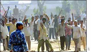 Gujarat mob watched by a member of the security forces