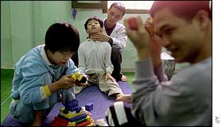 Duong Tien Thanh, in white jacket at background, gives physiotherapy to Le Trung Kien,12,  at the Thanh Xuan, Peace Village for handicapped children in Hanoi