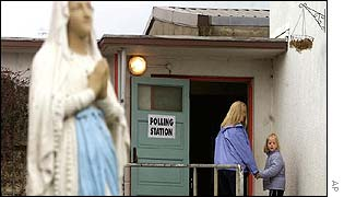Statue outside polling station, voters entering