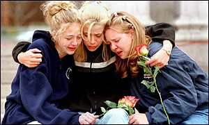 Teenagers comfort each other at a memorial to Columbine victims