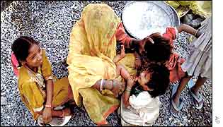 A woman sits with her children in Delhi
