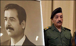 Iraqi Vice-President Taha Yasin Ramadan makes his way around a conference portrait of Saddam
