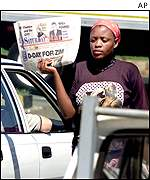 Street vendor in Harare holds up local paper with headline