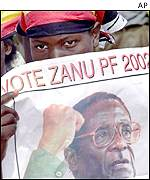 A ruling party ZANU-PF supporter holds an election poster