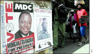Zimbabweans walk past posters of Morgan Tsvangirai and Robert Mugabe