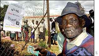 An old man holding his ID card at a polling station