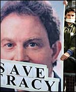 Human rights campaigners with a poster showing a gagged Tony Blair