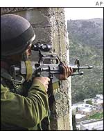 An Israeli soldier trains his rifle on the valley near Deheishe refugee camp