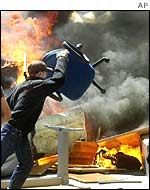 A protester throws a chair onto a barricade in Genoa