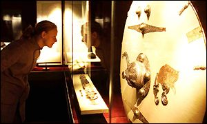 A visitor looks at a sword and shield