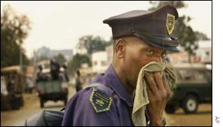 A police officer covers his face