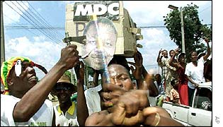 Mugabe supporter holds axe to poster of opposition leader