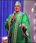 Louis Farrakhan preaching wearing a green robe
