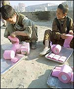 Boys cut up toilet rolls