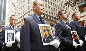 New York firefighters carry pictures of their friends, relatives and colleagues who were killed in the 11 September attacks